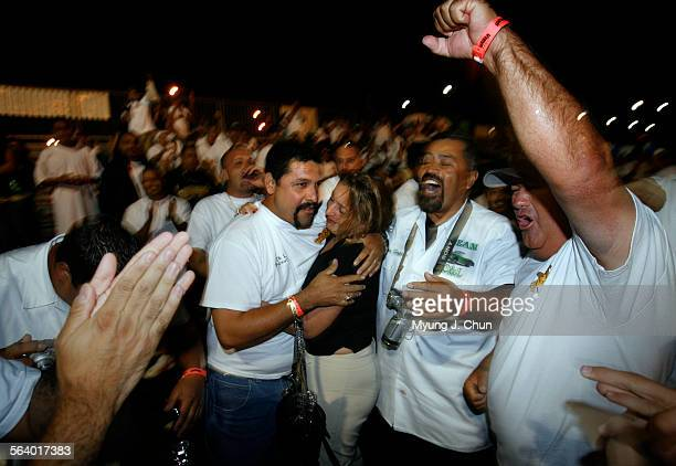 Alejandro Chino Vega with his wife Jessenia and members of the UCE Car Club celebrate his win for the Best Car in Show award Sunday night following...