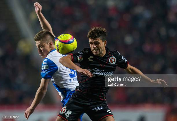 Alejandro Chumacero of Puebla and Ignacio Rivero of Tijuana compete for the ball during the 4th round match between Tijuana and Puebla as part of the...