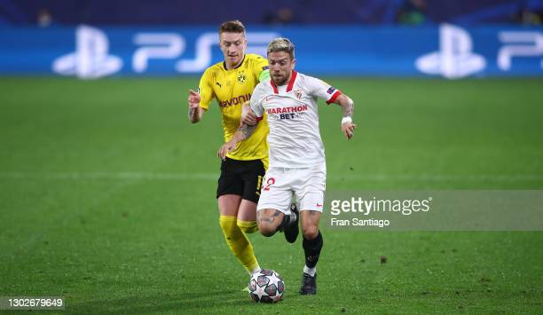 Alejandro Dario Gomez of Sevilla is challenged by Marco Reus of Borussia Dortmund during the UEFA Champions League Round of 16 match between Sevilla...