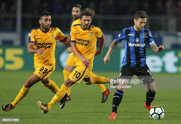 Alejandro Dario of Atalanta BC is challenged by Alessio Cerci and Mohamed Fares of Hellas Verona FC during the Serie A match between Atalanta BC and...