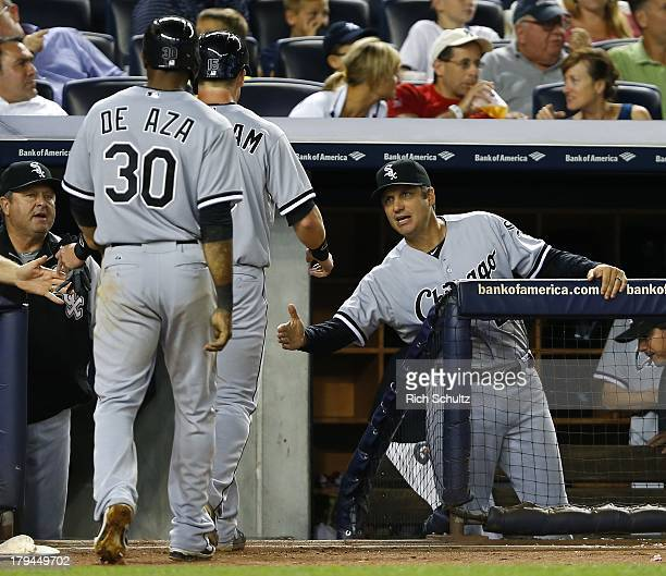Alejandro De Aza and Gordon Beckham of the Chicago White Sox are congratulated by manager Robin Ventura after scoring on a triple by Alexei Ramirez...