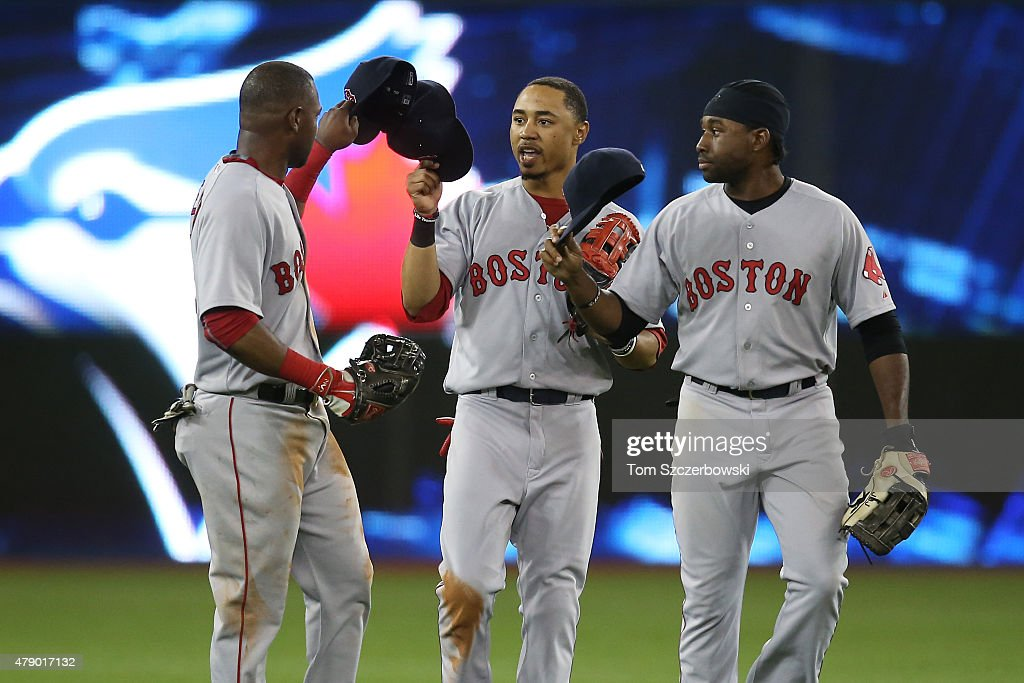 Alejandro De Aza #31 of the Boston Red Sox celebrates a victory with Mookie Betts #50 and Jackie Bradley #25 after MLB game action against the Toronto Blue Jays on June 29, 2015 at Rogers Centre in Toronto, Ontario, Canada.