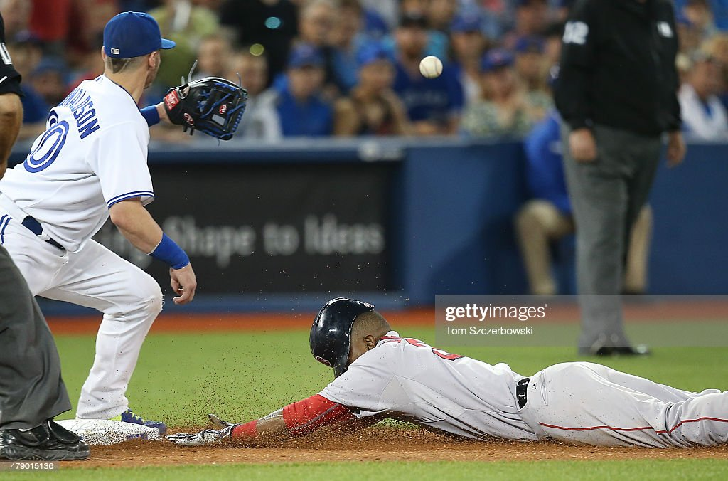 Alejandro De Aza #31 of the Boston Red Sox slides into third base with a triple in the ninth inning during MLB game action as Josh Donaldson #20 of the Toronto Blue Jays waits for the throw on June 29, 2015 at Rogers Centre in Toronto, Ontario, Canada.