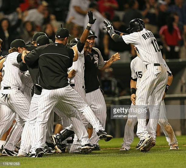 Alejandro De Aza of the Chicago White Sox celebrates with teammates including Alexei Ramirez after getting the gamewinning hit a tworun double in the...