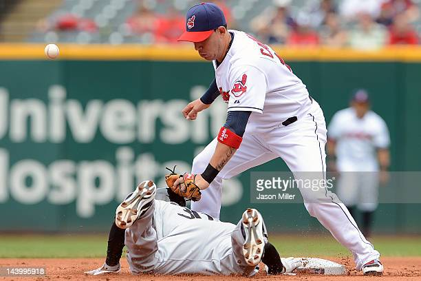 Alejandro De Aza of the Chicago White Sox dives back to the base as shortstop Asdrubal Cabrera of the Cleveland Indians misses the throw during the...