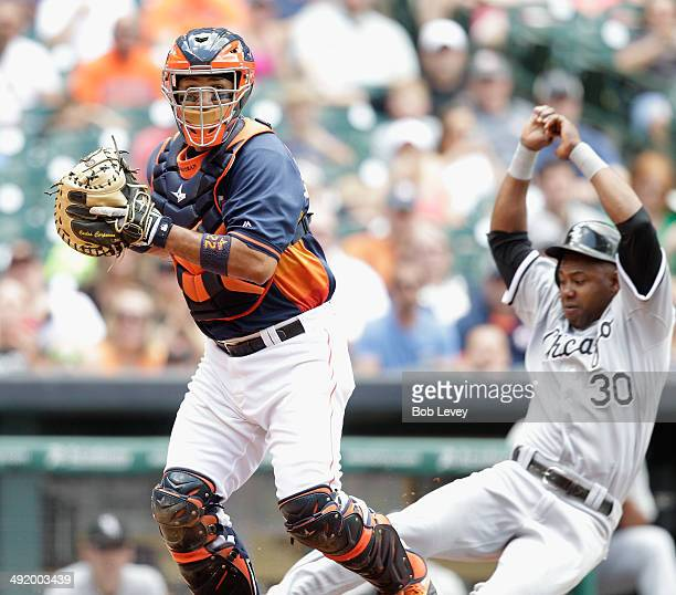 Alejandro De Aza of the Chicago White Sox is forced out at home as Carlos Corporan of the Houston Astros throws to first to complete a double play at...