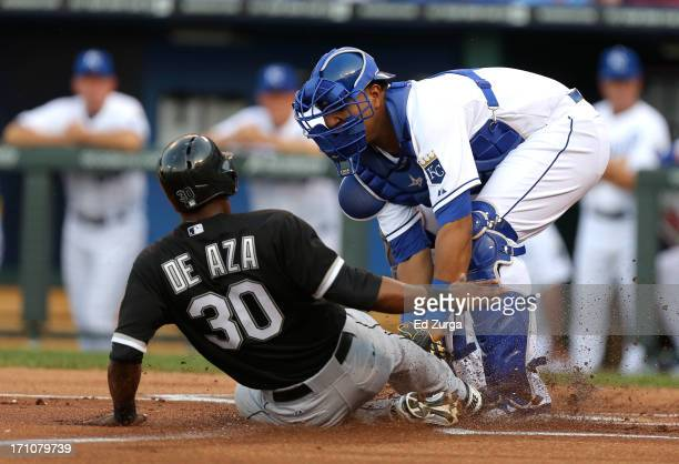 Alejandro De Aza of the Chicago White Sox is tagged out at home by Salvador Perez of the Kansas City Royals as he tries to score on a fielder's...
