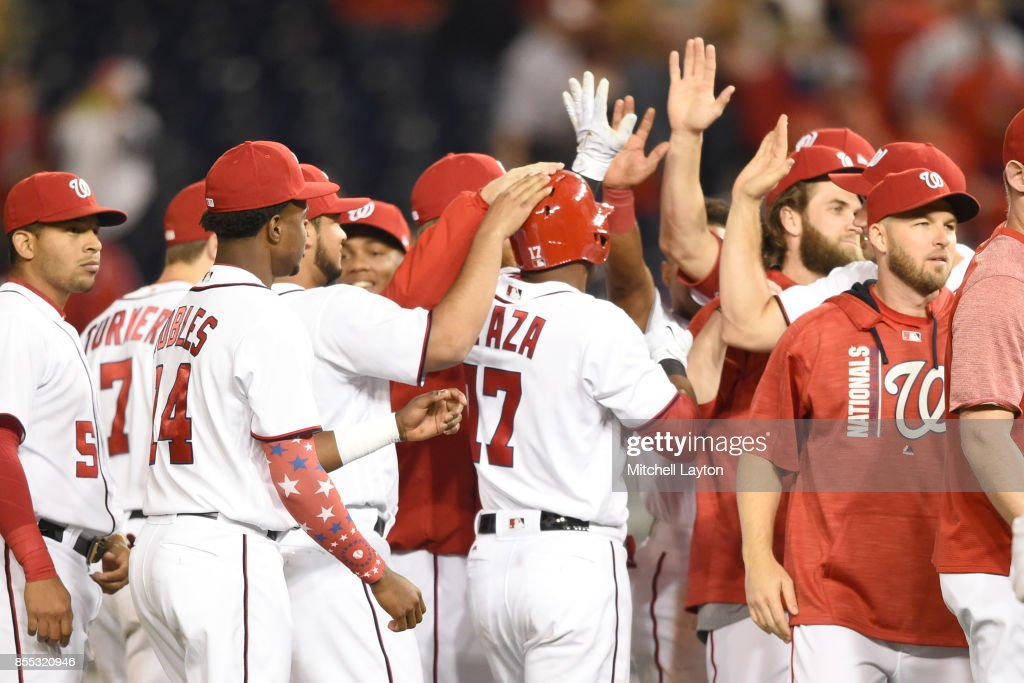 Alejandro De Aza #17 of the Washington Nationals celebrates with teammates after getting a game-winning hit in the ninth inning during a baseball game against the Pittsburgh Pirates at Nationals Park on September 28, 2017 in Washington, DC.