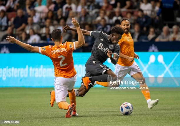 Alejandro Fuenmayor of Houston Dynamo tackles Alphonso Davies of Vancouver Whitecaps with Arturo Alvarez of Houston Dynamo at BC Place on May 11 2018...