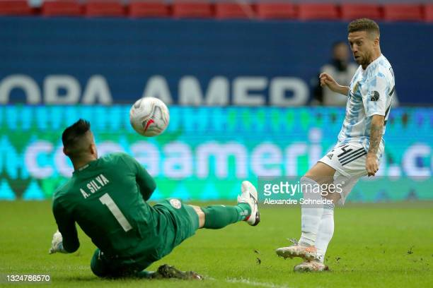 Alejandro Gomez of Argentina kicks the ball over Antony Silva goalkeeper of Paraguay to score the first goal of his team during a group A match...