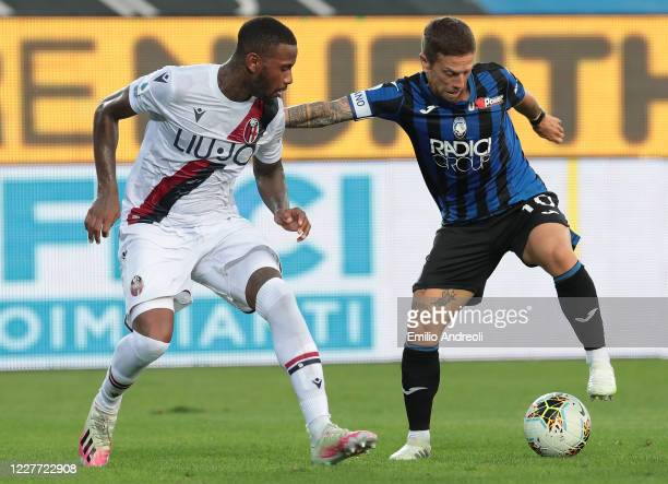 Alejandro Gomez of Atalanta BC is challenged by Stefano Denswill of Bologna FC during the Serie A match between Atalanta BC and Bologna FC at Gewiss...