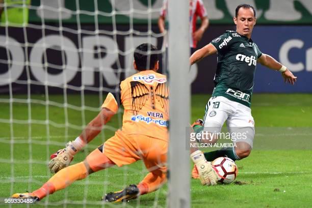 Alejandro Guerra of Brazil's Palmeiras vies for the ball with goalkeeper Mario Viera of Colombia's Junior during their 2018 Copa Libertadores...