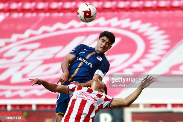 Alejandro Ibanez of Atletico de San Luis fights for the ball with Gilberto Sepulveda of Chivas during the 5th round match between Chivas and Atletico...