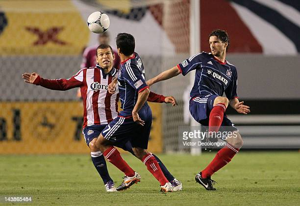 Alejandro Moreno of Chivas USA and Pavel Pardo and Arne Friedrich of the Chicago Fire vie for the ball in the first half during the MLS match at The...