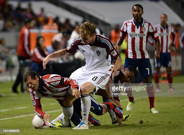 Alejandro Moreno of Chivas USA is knocked to the ground by Tyson Wahl and Jaime Castrillon of the Colorado Rapid during a 20 Rapid win at The Home...