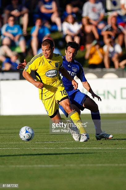 Alejandro Moreno of the Columbus Crew dribbles away from Kerry Zavagnin of the Kansas City Wizards during the game at Community America Ballpark on...