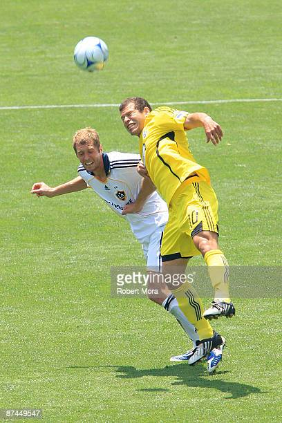 Alejandro Moreno of the Columbus Crew leaps over Gregg Berhalter of the Los Angeles Galaxy for a loose ball during their MLS game at The Home Depot...