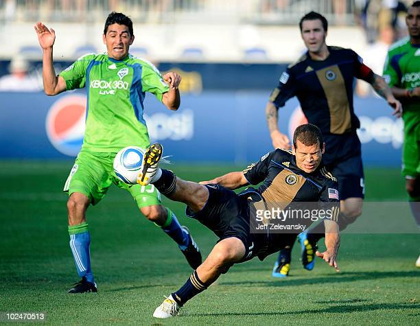 Alejandro Moreno of the Philadelphia Union kicks the ball in front of Leo Gonzalez of the Seattle Sounders FC at the PPL Park stadium opener on June...