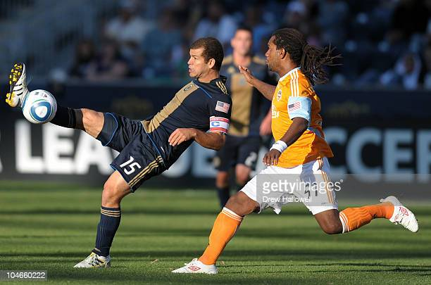 Alejandro Moreno of the Philadelphia Union kicks the ball past an approaching Adrian Serioux of the Houston Dynamo at PPL Park on October 2 2010 in...