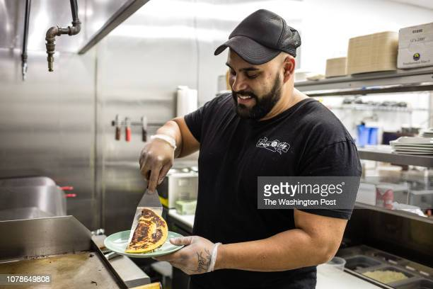 Alejandro Osorio owner of Arepa Lady a Colombian restaurant makes an arepa with cheese Tuesday December 18 in Jackson Heights New York It is...