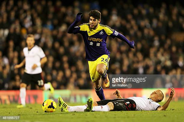 Alejandro Pozuelo of Swansea leaps over the challenge from Brede Hangeland of Fulham during the Barclays Premier League match between Fulham and...