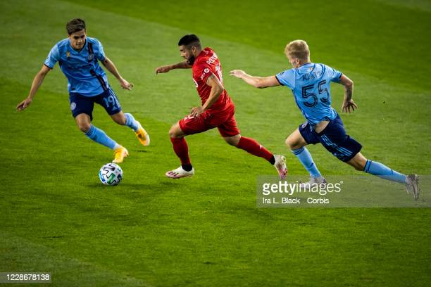 Alejandro Pozuelo of Toronto FC tries to get past Keaton Parks of New York City and Jesus Medina of New York City during the first half of the Major...