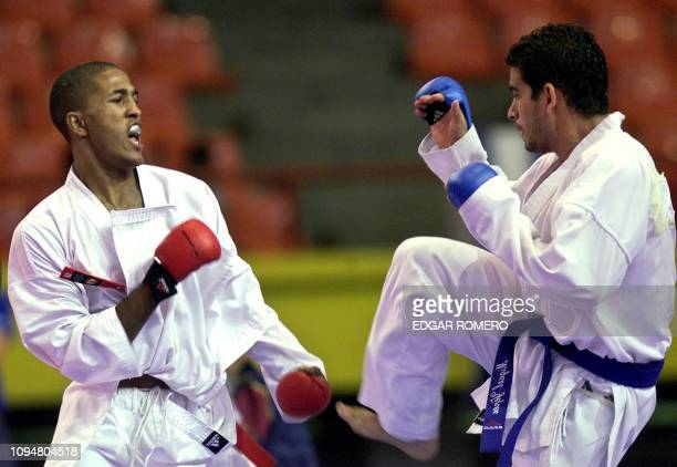Alejandro Yepez of Venezuela connect kicked 25 November 2002 the Dominican Alberto Zabala during the Karate Do competition in the 60kg category of...