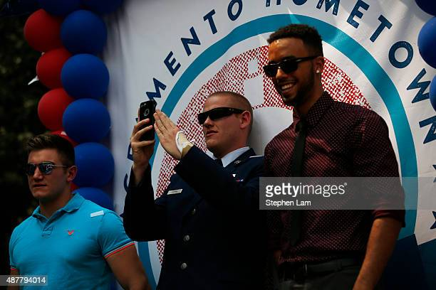 Alek Skarlatos and Anthony Sadler watch the crowd as Spencer Stone takes photographs with his phone during a parade honoring their August 21 actions...