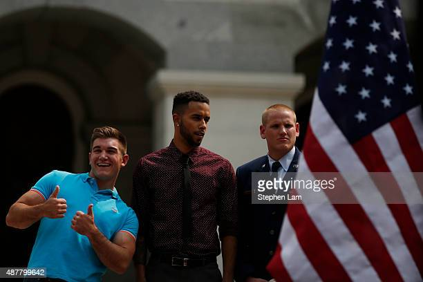 Alek Skarlatos gestures to the crowd as Anthony Sadler and Spencer Stone stand on stage during a parade honoring their August 21 actions in...