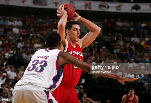 Aleks Maric of the Nebraska Cornhuskers looks to pass inside the paint against CJ Giles of the Kansas Jayhawks during the semifinals round of the...