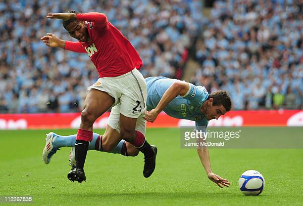 Aleksandar Kolarov of Manchester City and Antonio Valencia of Manchester United clash during the FA Cup sponsored by E.ON semi final match between...