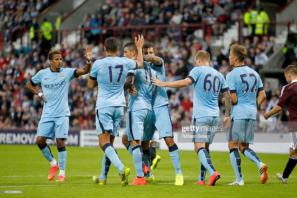 Aleksandar Kolarov of Manchester City by team mates after scoring and making 2-1 from the penalty spot during the pre-season friendly at Tynecastle Stadium on July 18, 2014 in Edinburgh, Scotland.