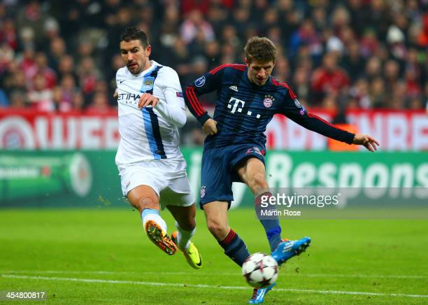 Aleksandar Kolarov of Manchester City can't stop Thomas Mueller of Bayern Muenchen scoring their first goal during the UEFA Champions League Group D...