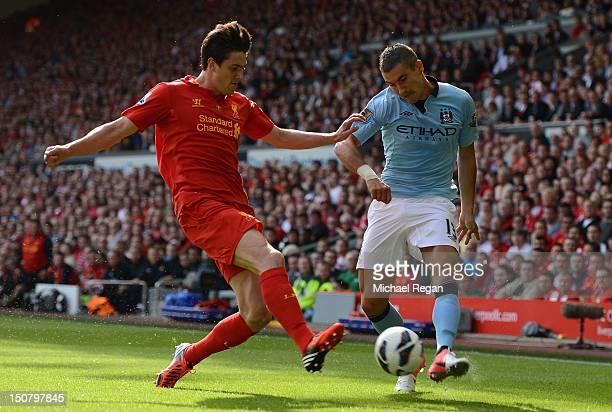 Aleksandar Kolarov of Manchester City competes with Martin Kelly of Liverpool during the Barclays Premier League match between Liverpool and...