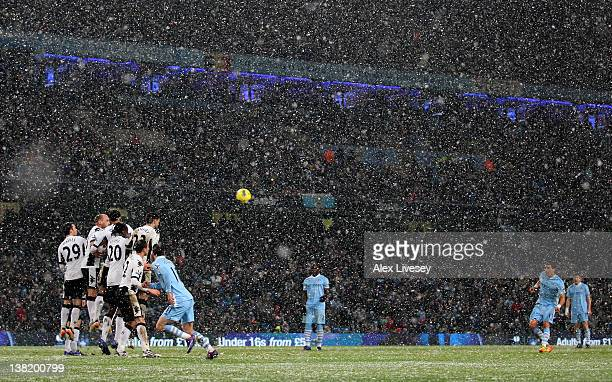 Aleksandar Kolarov of Manchester City fires in a free kick as snow falls during the Barclays Premier League match between Manchester City and Fulham...