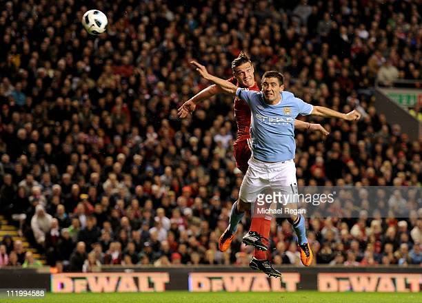 Aleksandar Kolarov of Manchester City is unable to stop Andy Carroll of Liverpool scoring his team's third goal during the Barclays Premier League...