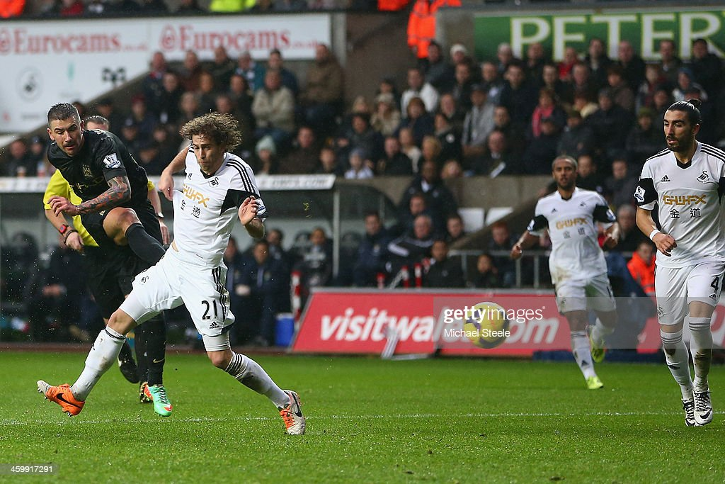 Aleksandar Kolorov (L) of Manchester City fires in his sides third goal past the challenge of Jose Canas of Swansea City during the Barclays Premier League match between Swansea City and Manchester City at the Liberty Stadium on January 1, 2014 in Swansea, Wales.
