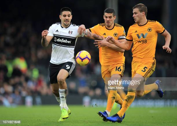 Aleksandar Mitrovic of Fulham is challenged by Conor Coady of Wolverhampton Wanderers and Ryan Bennett of Wolverhampton Wanderers during the Premier...