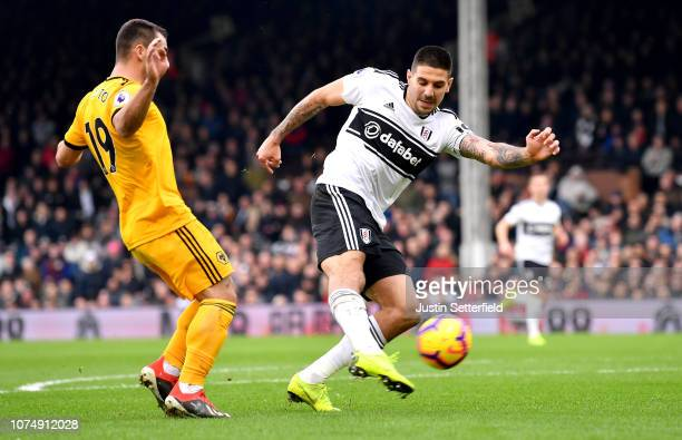 Aleksandar Mitrovic of Fulham shoots while under pressure from Jonny Otto of Wolverhampton Wanderers during the Premier League match between Fulham...