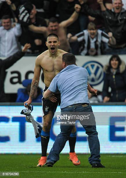 Aleksandar Mitrovic of Newcastle celebrates with his shirt off to a fan who invaded the pitch after scoring the equalising goal during the Premier...