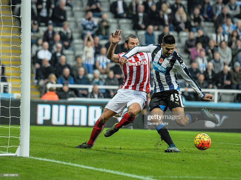 Aleksandar Mitrovic of Newcastle (R) strikes the ball whilst being tackled by Eric Pieters (L) of Stoke City during the Barclays Premier League match between Newcastle United and Stoke City at St.James' Park on October 31, 2015, in Newcastle upon Tyne, England.