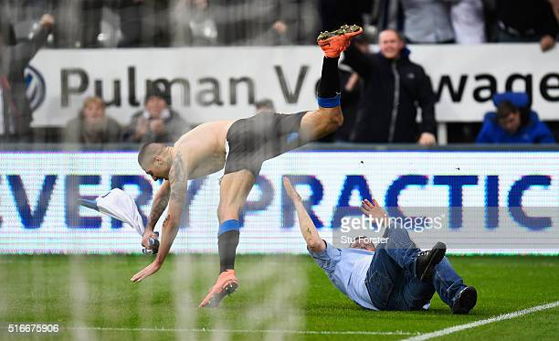 Aleksandar Mitrovic of Newcastle United collides with a fan as he celebrates scoring their first and equalising goal during the Barclays Premier...