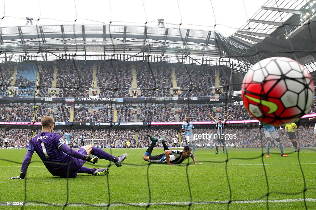 Aleksandar Mitrovic of Newcastle United scores his team's first goal past Joe Hart of Manchester City during the Barclays Premier League match between Manchester City and Newcastle United at Etihad Stadium on October 3, 2015 in Manchester, United Kingdom.