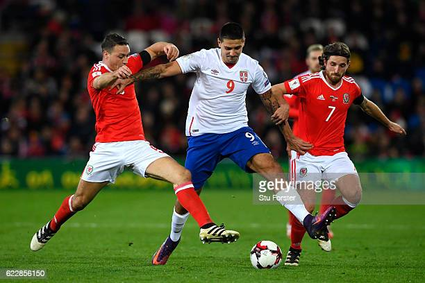 Aleksandar Mitrovic of Serbia battles with James Chester and Joe Allen of Wales during the FIFA 2018 World Cup Qualifier between Wales and Serbia at...