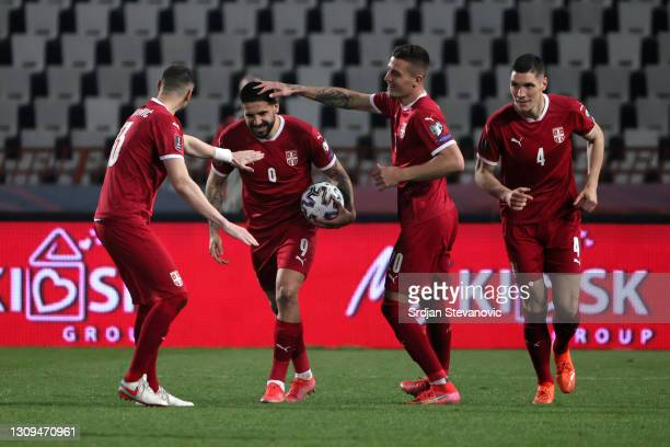 Aleksandar Mitrovic of Serbia celebrates with Sergej Milinkovic­-Savic and Stefan Mitrovic after scoring their team's first goal during the FIFA...