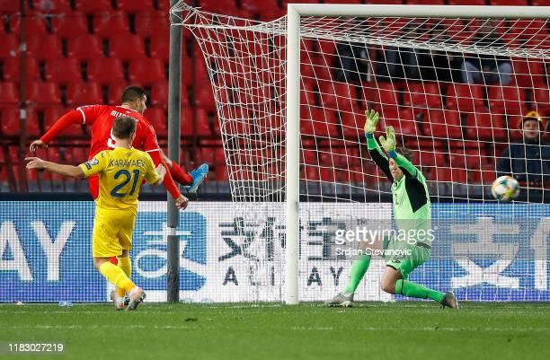 Aleksandar Mitrovic of Serbia scores a goal between Oleksandr Karavaev and goalkeeper Andriy Pyatov of Ukraine during the UEFA Euro 2020 Qualifier...