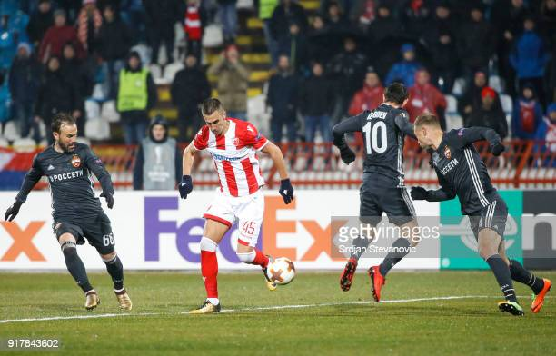 Aleksandar Pesic of Crvena Zvezda in action against Bibras Natcho and Alan Dzagoev of CSKA Moscow during UEFA Europa League Round of 32 match between...