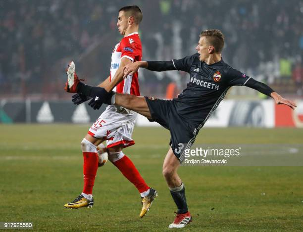 Aleksandar Pesic of Crvena Zvezda is challenged by Pontus Wernbloom of CSKA Moscow during the UEFA Europa League Round of 32 match between Crvena...