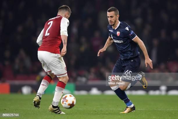 Aleksandar Pesic of FK Crvena Zvezda attempts to get past Mathieu Debuchy of Arsenal during the UEFA Europa League group H match between Arsenal FC...