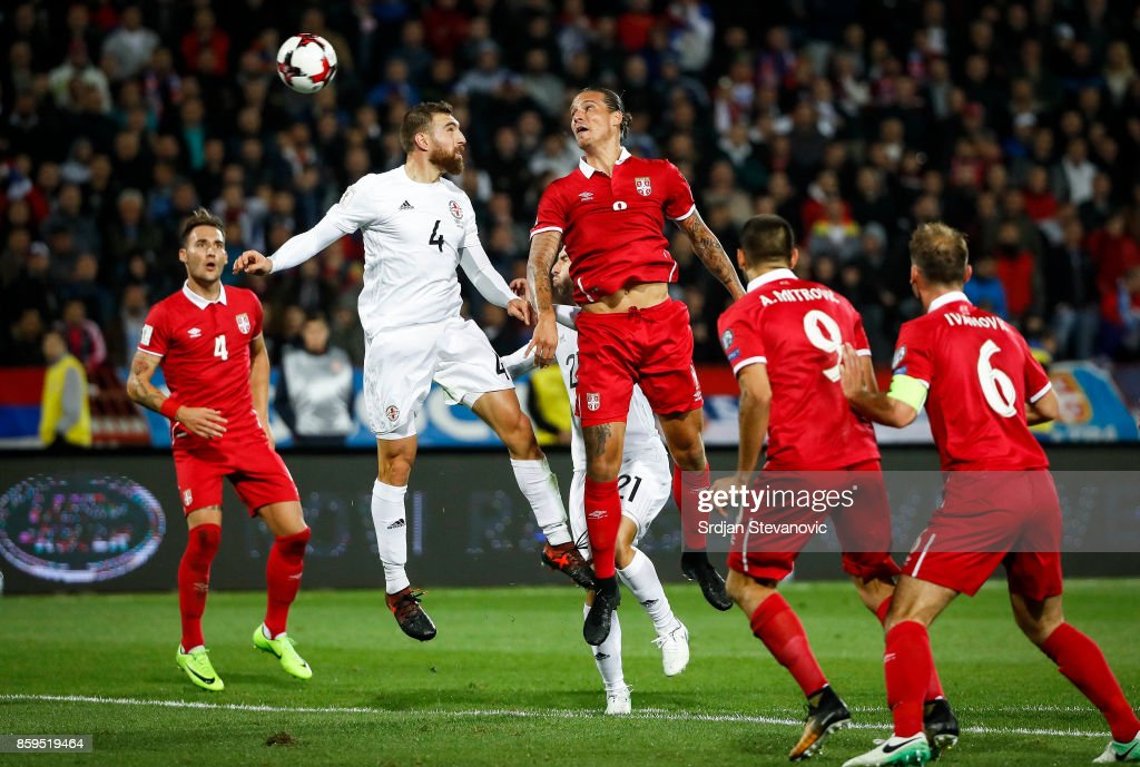 Aleksandar Prijovic (R) of Serbia jump for the ball against Guram Kashia (L) of Georgia during FIFA 2018 World Cup Qualifier between Serbia and Georgia at stadium Rajko Mitic on October 9, 2017 in Belgrade.